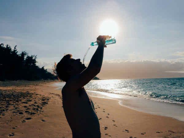 ragazzo si disseta in spiaggia