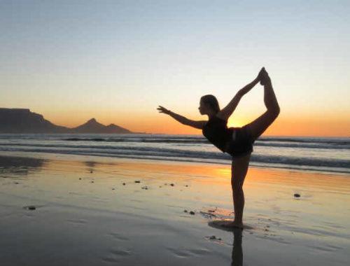 Ragazza fa yoga in spiaggia