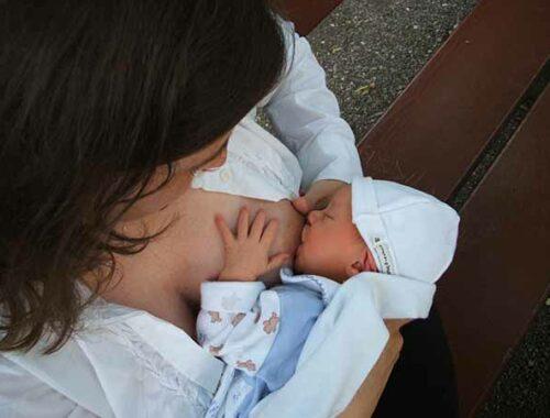 Madre allatta neonato al seno